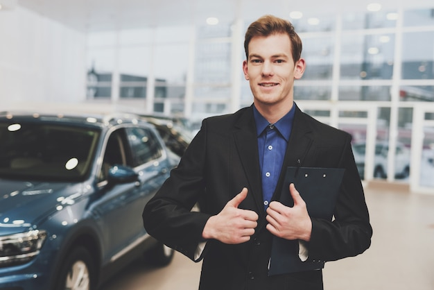 Formell gekleideter autohändler bietet autokredit an Premium Fotos
