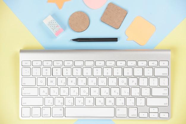 Formen; radiergummi und bleistift in der nähe der weißen tastatur auf doppeltem hintergrund Kostenlose Fotos