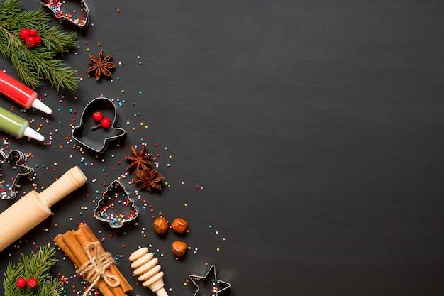 Formen und zutaten für die herstellung von weihnachtsplätzchen auf einem schwarzen hintergrund Premium Fotos