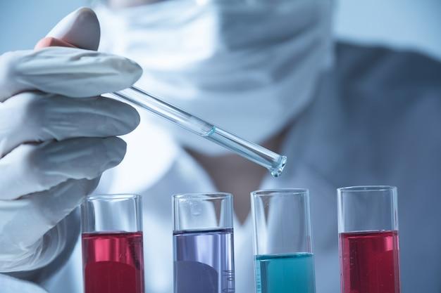 Forscher mit chemischen laborreagenzgläsern mit flüssigkeit Premium Fotos