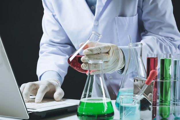 Forscher mit chemischen reagenzgläsern des glaslabors mit flüssigkeit Premium Fotos