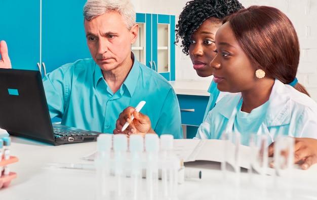 Fortschrittsbericht im prüflabor. weibliche afrikanische medizinstudenten, absolventen, die dem kaukasischen mann, dem wissenschaftlichen berater des senors, daten zeigen. führen sie in fällen von covid-19-lungenentzündung einen blut- und pcr-test auf das coronavirus durch. Premium Fotos