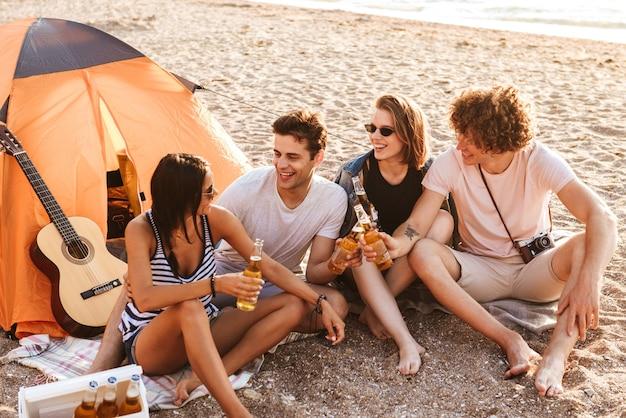 Foto der aufgeregten gruppe von freunden draußen am strand sitzend, während sie bier trinken, das miteinander spricht Premium Fotos