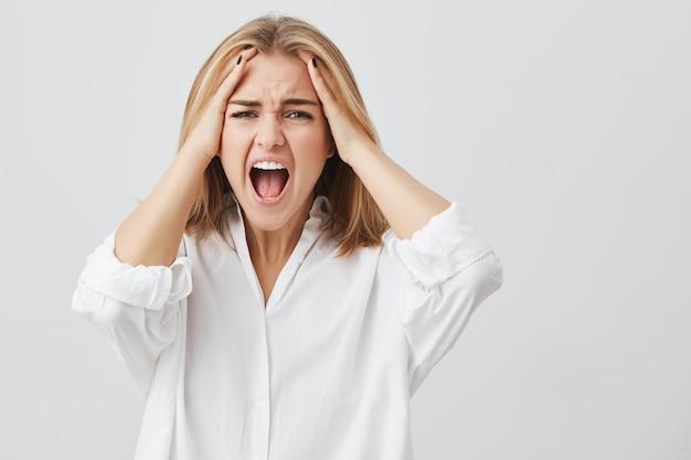 Foto der enttäuschten frau mit blondem haar, das ihre hände auf den stirnrunzeln hält, die das gesicht mit weit geöffnetem mund vor verzweiflung und schrecken schreien. Kostenlose Fotos