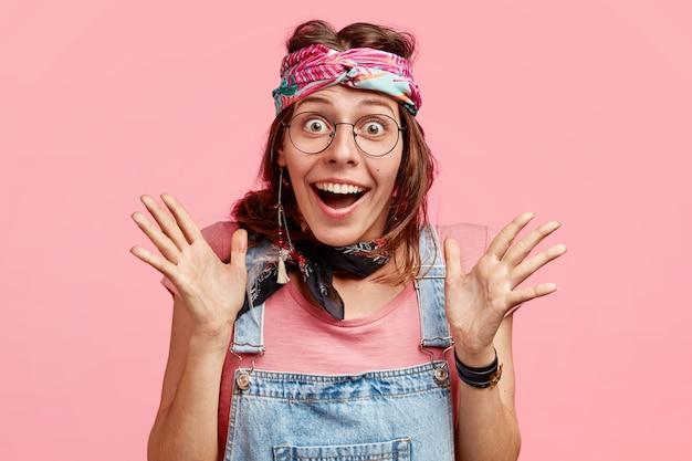 Foto der freudigen jungen frau mit glücklichem ausdruck, gesten mit den händen, hat überglücklichen ausdruck, erwartet nicht, etwas unglaubliches zu sehen, trägt brille und stirnband, isoliert auf rosa Kostenlose Fotos