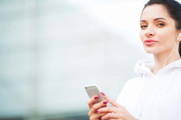 Foto der frohen eignungs-frau 30s in der sportkleidung, die bluetooth earpod berührt und handy hält, beim stillstehen im grünen park Premium Fotos
