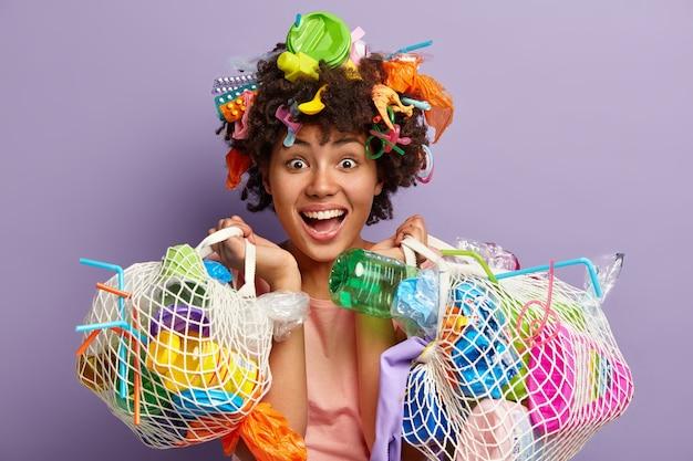 Foto der glücklichen jungen weiblichen freiwilligen trägt taschen mit abfall, sieht freudig aus, froh, gute dinge für umwelt und planeten zu tun, wo sie lebt, isoliert über lila wand. Kostenlose Fotos