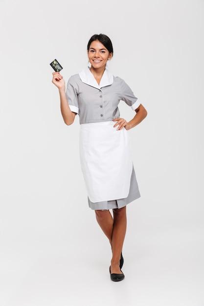 Foto der hübschen brünetten haushälterin in voller länge, die mit der hand auf ihrer taille steht und kreditkarte hält Kostenlose Fotos