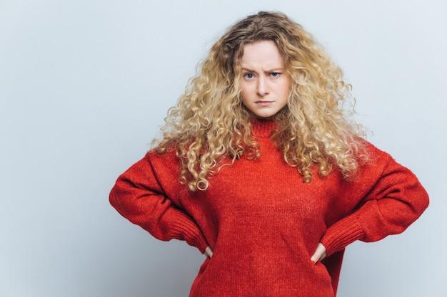 Foto der missfallenen verärgerten frau mit dem gelockten haar, hält hände auf taille Premium Fotos