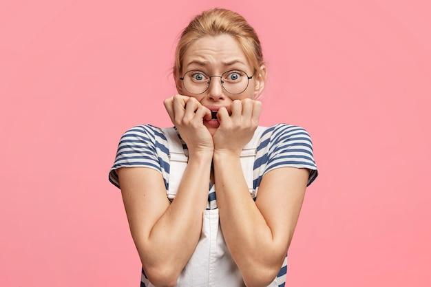 Foto der nervösen frau beißt fingernägel und schaut stressig in die kamera Kostenlose Fotos