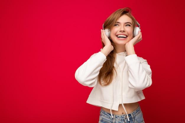 Foto der schönen glücklichen lächelnden jungen blonden frau, die weißen kapuzenpulli lokalisiert über bunt trägt Premium Fotos