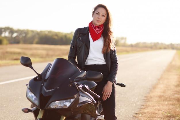 Foto der sorglosen bikerin gekleidet in modische kleidung Kostenlose Fotos