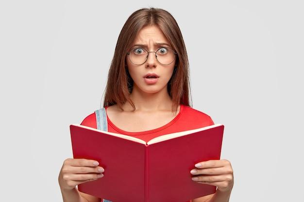 Foto der verblüfften emotionalen jungen kaukasischen frau schaut mit verblüffung, hält rotes buch, muss viel für die nächste lektion lernen, trägt runde brille, isoliert über weißer wand Kostenlose Fotos