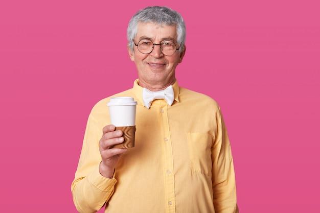 Foto des eleganten senioren, der pappbecher kaffee hält, bereit, heißes getränk zu trinken, gekleidet in formelles hemd und fliege, hat treffen, modelle auf rosiger studiowand mit leerem raum für ihre werbung. Kostenlose Fotos