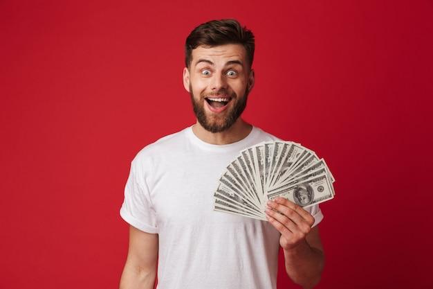 Foto des glücklichen europäischen mannes im lässigen t-shirt lächelnd und hält fan des geldes in den dollar-banknoten, lokalisiert über roter wand Premium Fotos