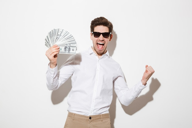 Foto des glücklichen gewinnermannes im hemd und in der sonnenbrille, die schreiend und fan des geldes in dollarbanknoten mit geballter faust halten, lokalisiert über weißer wand mit schatten Premium Fotos