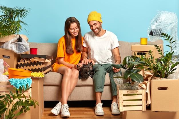 Foto des glücklichen jungen paares, das auf der couch sitzt, umgeben von kisten Kostenlose Fotos