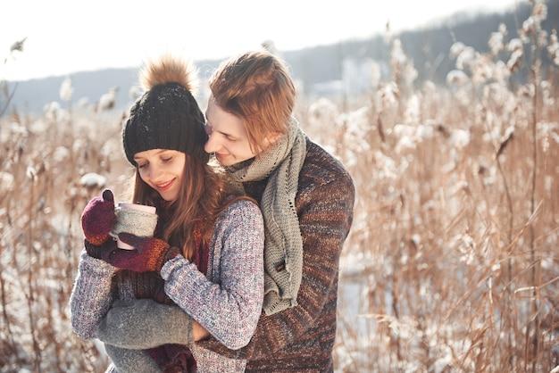 Foto des glücklichen mannes und der hübschen frau mit den schalen im freien im winter. winterurlaub und ferien. weihnachtspaare des glücklichen mannes und der frau trinken heißen wein. verliebtes pärchen Premium Fotos