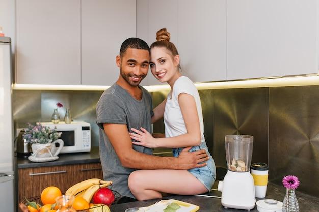 Foto des glücklichen paares in der küche. der ehemann legte seine frau in kurzen hosen auf den tisch. liebhaber, die sich umarmen. zeit zu hause teilen, auf gesichter lächeln. Kostenlose Fotos