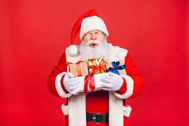 Foto des glücklichen weihnachtsmannes mit geschenkboxen Premium Fotos