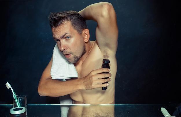Foto des gutaussehenden mannes, der seine achselhöhle rasiert. der junge mann im schlafzimmer sitzt zu hause vor dem spiegel. konzept der menschlichen haut und des lebensstils Kostenlose Fotos