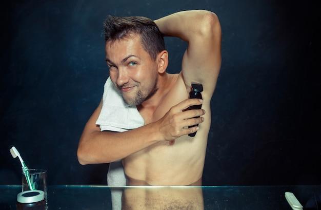 Foto des gutaussehenden mannes, der seine achselhöhle rasiert Kostenlose Fotos