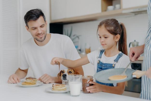 Foto des kleinen mädchens in den denimlatzhosen fügt schokolade pfannkuchen hinzu, frühstückt zusammen mit vati und hund, mag, wie mutter kocht. familie in der küche frühstücken am wochenende. glücklicher moment Premium Fotos