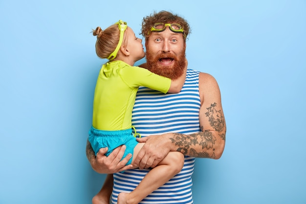 Foto des lustigen ingwervaters erhält umarmung und kuss von der kleinen tochter, trägt kind auf händen, trägt schwimmbrille, verbringt freizeit am schwimmbad, trägt freizeitkleidung, hat gute beziehung Kostenlose Fotos
