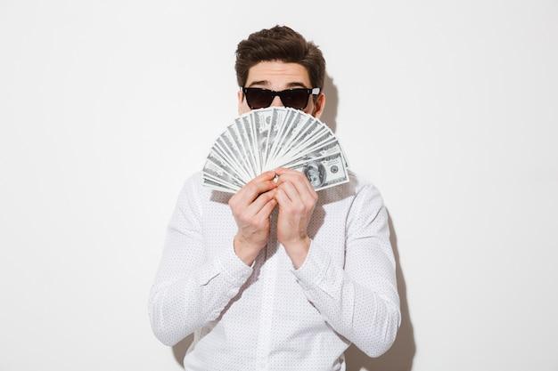 Foto des lustigen mannes im freizeithemd und in der sonnenbrille, die sein gesicht mit geldfächer in dollarwährung bedecken, lokalisiert über weißer wand mit schatten Premium Fotos