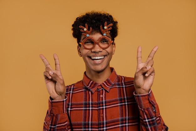 Foto des niedlichen afrikanischen männlichen bauern trägt weihnachtsbrille und lächelt, zeigt frieden und liebe. mann trägt kariertes hemd, isolierten braunen farbhintergrund. Premium Fotos