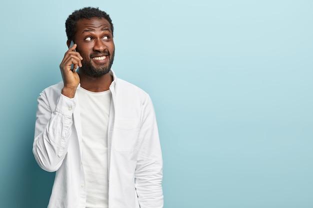 Foto des schwarzen ethnischen hipster-mannes hat telefongespräch, hält handy nahe ohr, erzählt nachrichten zu freund, konzentriert weg, trägt weißes hemd. erfolgreicher geschäftsmann macht termin per handy Kostenlose Fotos