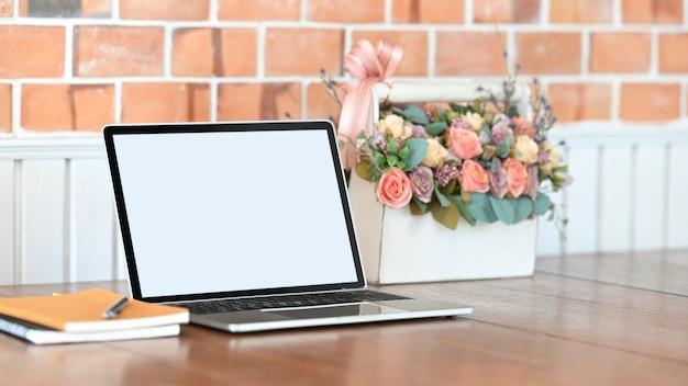 Foto des weißen leeren bildschirmlaptops, des notizbuchs, des stiftes und des rosenstraußes in dem weißen plastikkorb, der auf den holztisch mit betonwand als hintergrund setzt. Premium Fotos