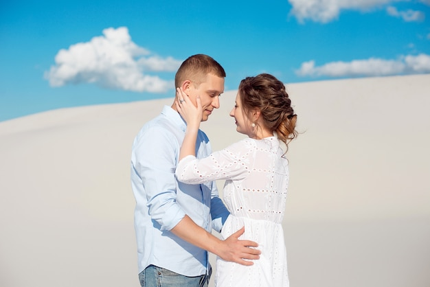 Foto eines herrlichen paares mann und frau lächelnd und umarmend auf einem sandigen hügel Premium Fotos