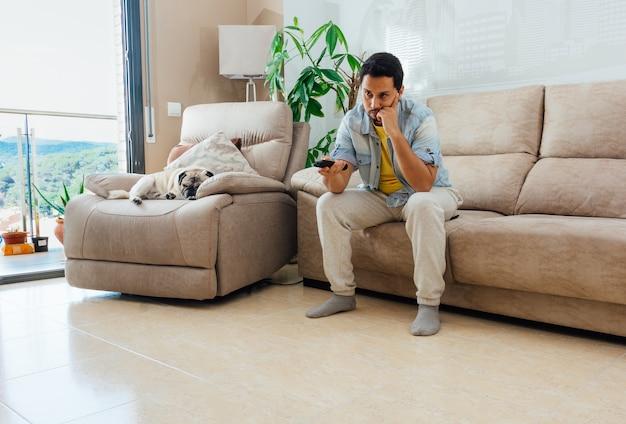 Foto eines hübschen hispanischen mannes, der auf einem sofa sitzt und fernsieht Kostenlose Fotos