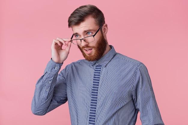 Foto eines jungen attraktiven bärtigen mannes, der missbilligend durch seine brille blickte, machte kollege einen dummen fehler bei der arbeit. isoliert über rosa hintergrund. Kostenlose Fotos