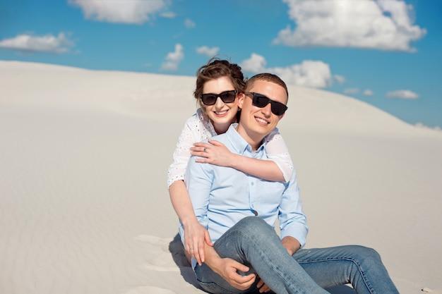 Foto eines wunderschönen paares mann und frau lächelnd und umarmend auf einem sandhügel. Premium Fotos
