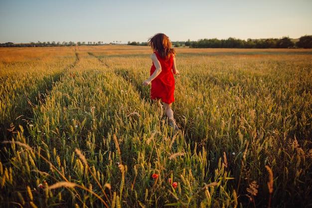 Foto herrlicher dame im roten kleid, das auf dem goldenen sommergebiet steht Kostenlose Fotos