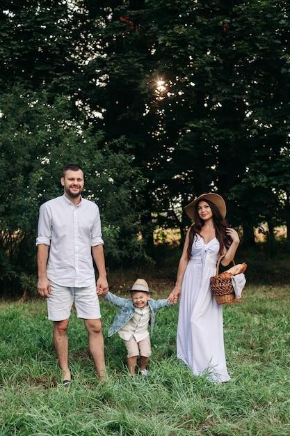Foto in voller länge von einem vater und einer mutter, die die hände ihres sohnes halten, die im sommerpark in den bäumen stehen. frau in hut und kleid hält einen braunen korb mit essen für picknick. Premium Fotos