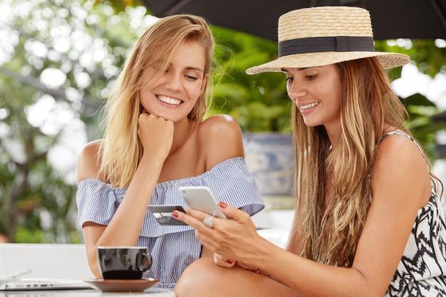 Foto von angenehm aussehenden zwei frauen haben ruhe im café, wählen sie neuen kauf. attraktive junge frau wählt nummer der kreditkarte auf dem handy, zahlt online. menschen- und freizeitkonzept Kostenlose Fotos