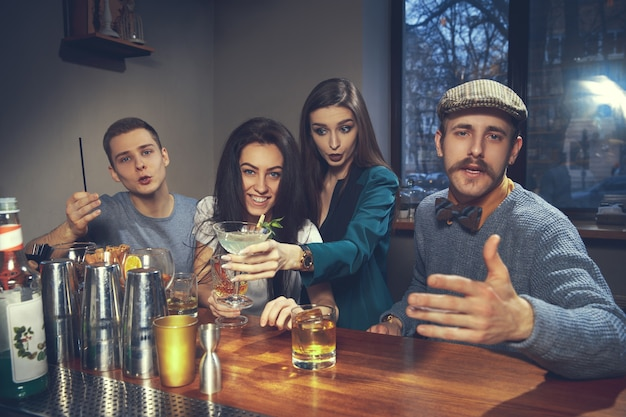 Foto von freudigen freunden in der bar oder in der kneipe, die miteinander kommunizieren Kostenlose Fotos