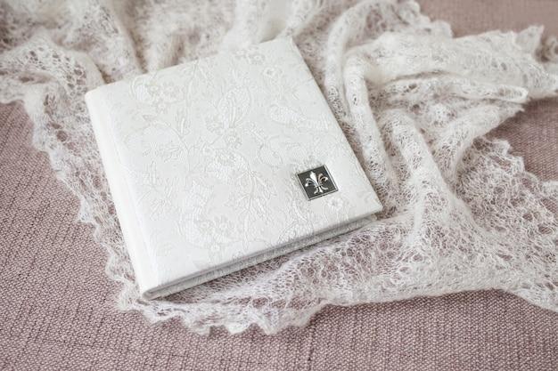 Fotobuch mit einem umschlag aus echtem leder. weiße farbe mit dekorativer prägung. weicher fokus. Premium Fotos