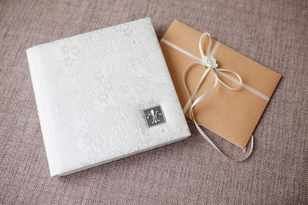 Fotobuch mit einem umschlag aus echtem leder. weiße farbe mit durchbrochener prägung. weicher fokus. Premium Fotos
