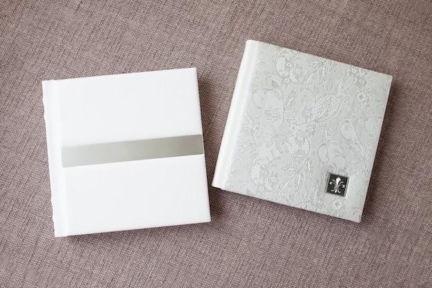 Fotobücher mit einem umschlag aus echtem leder. weiße farbe mit dekorativer prägung. weicher fokus. Premium Fotos