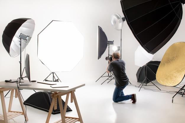 Fotograf arbeitet im modernen lichtstudio mit vielen arten von blitzlicht und zubehör Premium Fotos