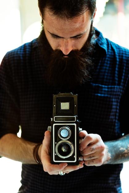 Fotograf, der eine weinlesekamera verwendet Kostenlose Fotos