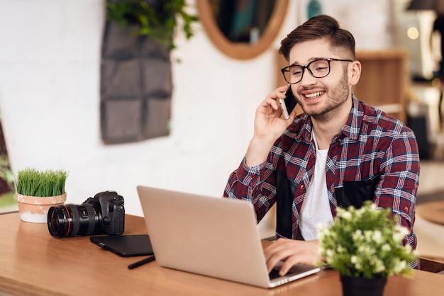 Fotograf-freiberufler spricht telefon beim arbeiten. Premium Fotos