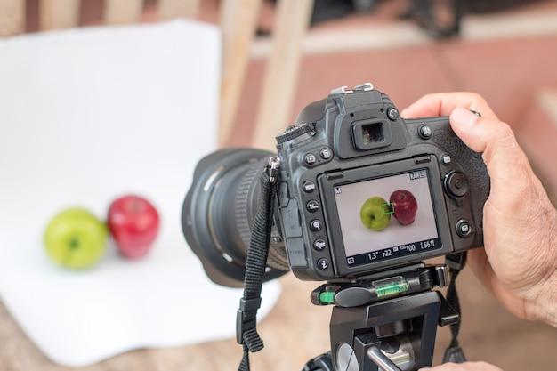 Fotografen verwenden dslr kamera schießen obst auf weißem hintergrund auswählen fokus kamera Premium Fotos