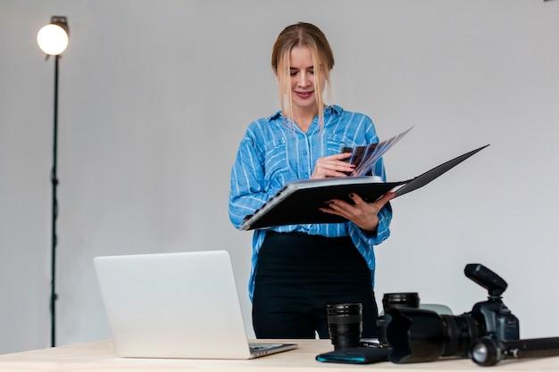 Fotograffrau, die durch ein fotoalbum grast Premium Fotos