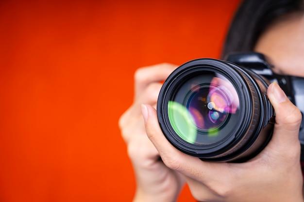 Fotografie hintergrundkonzept. nahaufnahme des fotografen, der eine kamera auf rotem hintergrund verwendet. Premium Fotos
