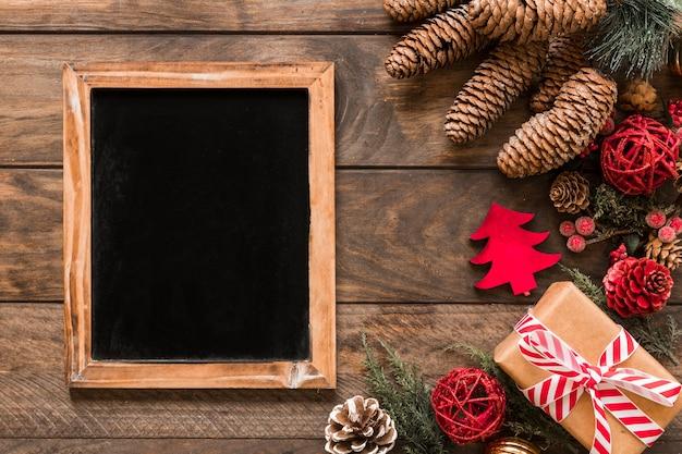 Fotorahmen in der nähe von geschenkbox, tannenzweigen, ziergegenständen und weihnachtskugeln Kostenlose Fotos